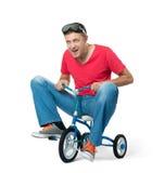 Den nyfikna mannen på barns cykel, på vit bakgrund royaltyfria foton