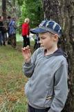 Den nyfikna pojken studerar invånarna av skogen Royaltyfria Foton