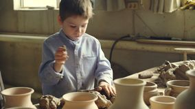 Den nyfikna pysen spelar med lera på den funktionsdugliga tabellen i seminariet för keramiker` som s knådar lera och river in i s stock video