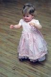 Den nyfikna små flickan som går i rosa färg, klär på trä däckar Arkivbild