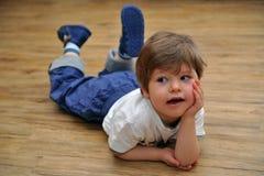 Den nyfikna små pojken som ligger på trä, däckar royaltyfri bild