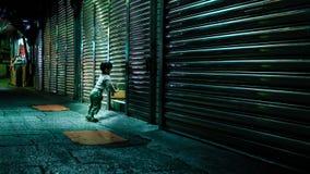 Den nyfikna unga pojken stänger glidningsdörren av hans stannar royaltyfria foton