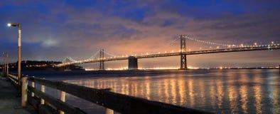 Den Oakland fjärdbron tänder i skymning i San Francisco, Kalifornien Arkivbild