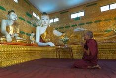 Den odefinierade munken ber på den Shwethalyaung Buddha på Januari 06, 2011 Fotografering för Bildbyråer