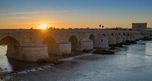 Den oerhörda romerska bron över floden Guadalquivir på den forntida moorish staden av Cordoba på solnedgången royaltyfria foton