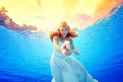 Den oerhörda skönhetrödhårig manflickan simmar undervattens- i en bröllopsklänning på solnedgången Royaltyfria Bilder