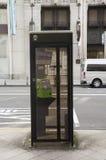 Den offentliga telefonen på bana bredvid trafikvägen för folk använder p arkivbilder