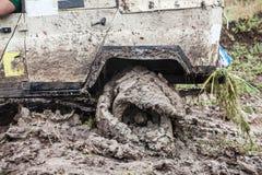 Den Offroad bilen klibbade i djup gyttja med det plana däcket Arkivfoto