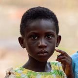 Den oidentifierade Ashanti flickan ser framåt i den lokala byn aseptic arkivbilder