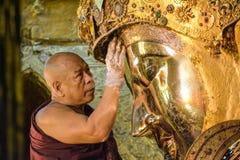 Den oidentifierade Burmese munken gör ren Buddhastatyn med det guld- papperet på den Mahamuni Buddhatemplet, Augusti Fotografering för Bildbyråer