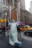 Den oidentifierade gataaktören poserar som en staty av frihet framtill av musik Hall för staden för den New York City gränsmärkera Arkivbilder