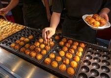 Den oidentifierade kocken lagar mat takoyaki på dotonborigatan i Osaka, J royaltyfria bilder