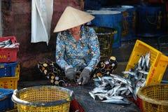Den oidentifierade kvinnan bearbetar fisken på Qui Nhon fiskport, Vietnam i morgonen Arkivfoto