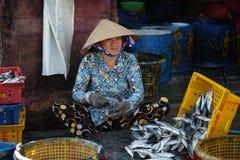 Den oidentifierade kvinnan bearbetar fisken på Qui Nhon fiskport, Vietnam i morgonen Royaltyfri Fotografi