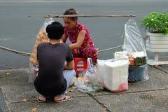 Den oidentifierade kvinnan säljer banhmien (traditionellt vietnamesiskt bröd) på gatan i Saigon, Ho Chi Minh City Royaltyfri Bild