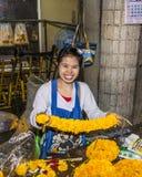 Den oidentifierade kvinnan säljer blommor på blommamarknaden Arkivfoton