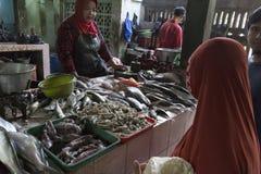 Den oidentifierade kvinnan säljer den nya fisken Royaltyfri Foto