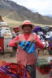 Den oidentifierade kvinnan säljer ullhattar på den Limite lilla medicinflaskan Puno region peru royaltyfria bilder