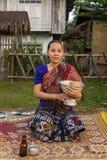 Den oidentifierade laokvinnan väntar på buddistmunkar att ge dem allmosa Arkivbilder