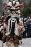 Den oidentifierade mannen i den traditionella Kukeri dräkten ses på festivalen av maskeradlekarna Kukerlandia i Yambol, Bulgarien Arkivbild
