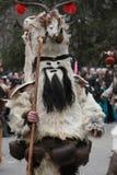 Den oidentifierade mannen i den traditionella Kukeri dräkten ses på festivalen av maskeradlekarna Kukerlandia i Yambol, Bulgarien Royaltyfri Bild