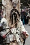Den oidentifierade mannen i den traditionella Kukeri dräkten ses på festivalen av maskeradlekarna Kukerlandia i Yambol, Bulgarien Arkivfoton