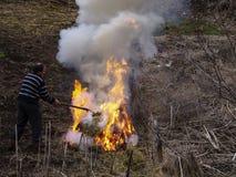 Den oidentifierade mannen matar en brinnande hög som förbereder hans gård för den växande säsongen på Shiroka Laka, Bulgarien royaltyfri fotografi