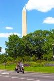 Den oidentifierade mannen reser på mopeden med den nationella monumentet som ses på bakgrunden Royaltyfri Bild