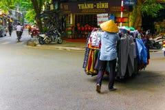 Den oidentifierade mannen skjuter shoppingvagnen med kläder i Hanoi, Vietnam arkivbilder