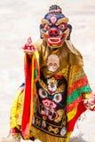 Den oidentifierade munken utför en maskerad och kostymerad gåtadans för klosterbroder av tibetan buddism Royaltyfri Foto