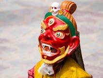 Den oidentifierade munken utför en maskerad och kostymerad gåtadans för klosterbroder av tibetan buddism Royaltyfri Bild