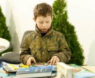 Den oidentifierade pojken läser försiktigt böcker på barn ställer ut Royaltyfri Bild