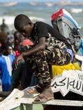 Den oidentifierade senegalesiska pojken i militärflåsanden står i boaen royaltyfri foto