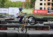 Den oidentifierade unga mannen rider hans BMX-cykel Arkivbild
