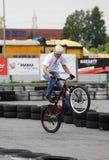 Den oidentifierade unga mannen rider hans BMX-cykel Arkivfoton