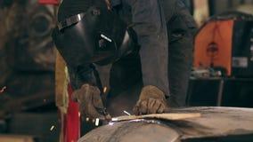 Den oigenkännliga arbetaren med svetsninghjälmen klipper på av metallstycket med en oxy bitande fackla för acetylen på ett mekani stock video
