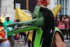 Den oigenkännliga dansaren som kläs som krokodil, går på gatan royaltyfria foton