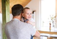 Den oigenkännliga fadern som rymmer hans gulligt, behandla som ett barn sonen i armarna Royaltyfria Bilder