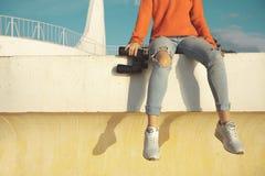 Den oigenkännliga flickahandelsresanden med kikare sitter på en balustrad och ser in i avståndet Fotografering för Bildbyråer