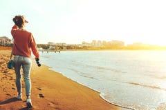 Den oigenkännliga fotvandrareflickan i jeans promenerar kusten med kikare, bakre sikt Spana Wanderlust Holidays Concept Royaltyfri Foto
