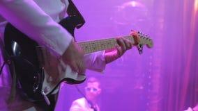 Den oigenkännliga gitarristen spelar gitarren på konsert arkivfilmer