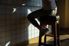Den oigenkännliga hipsterflickan sitter på en stol bak stången av ett stadigt kafé, en restaurangstång royaltyfri fotografi