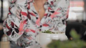 Den oigenkännliga kvinnliga turisten i en färgrik skjortasked äter en traditionell fransk löksoppa med krutonger, smältt ost stock video