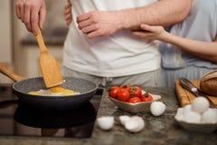 Den oigenkännliga kvinnlign och mannen steker tillsammans ägg och gör tomatsallad, står på kök, förbereder den involverade frukos royaltyfri fotografi