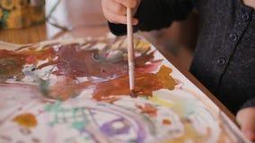 Den oigenkännliga liten flickablandningen målar på papper, närbildsikt lager videofilmer
