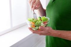 Den oigenkännliga mannen har sund lunch som äter bantar grönsaksallad Royaltyfri Foto