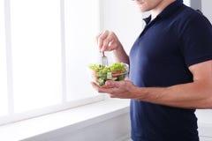 Den oigenkännliga mannen har sund lunch som äter bantar grönsaksallad Fotografering för Bildbyråer