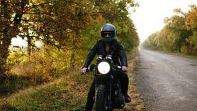 Den oigenkännliga mannen i det svarta hjälm- och läderomslaget som stoppar hans tappningmotorcykel på vägen, sid på solig höst stock video