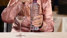 Den oigenkännliga pensionerade kvinnan sitter i restaurangen som öppnar en flaska av lugnt vatten Innehåll lutning- och urklippma stock video