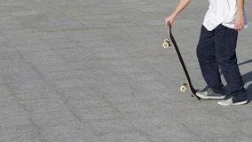 Den oigenkännliga skateboarderen sparkar upp en skateboard och tar en körning för att gå snabb stock video